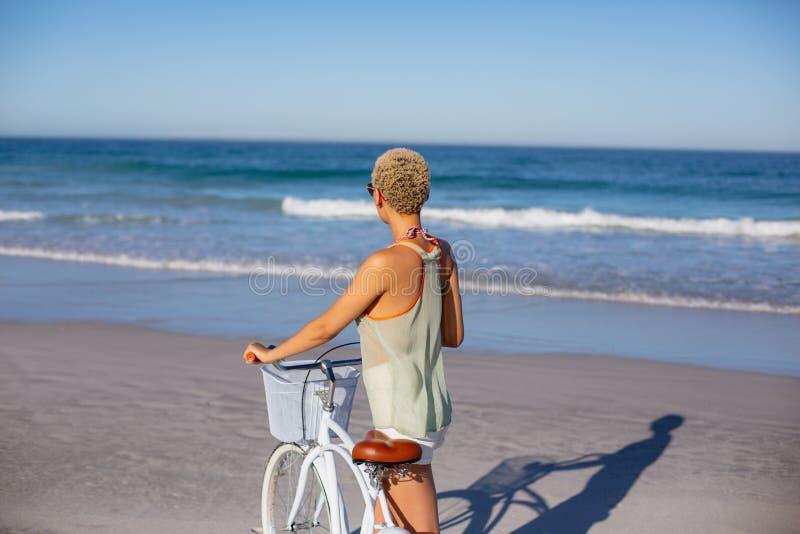 Положение женщины с велосипедом на пляже в солнечности стоковое фото