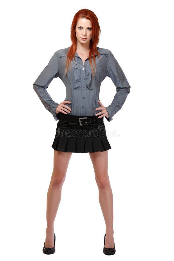 Положение женщины Redhead изолированное на белизне стоковое фото