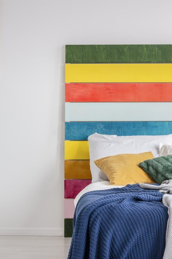 Положение картины радуги против белой стены, за уютной кроватью в белом интерьере спальни Реальное фото стоковое изображение