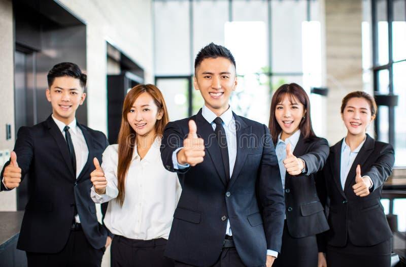 положение команды дела и показывать большие пальцы руки вверх стоковая фотография