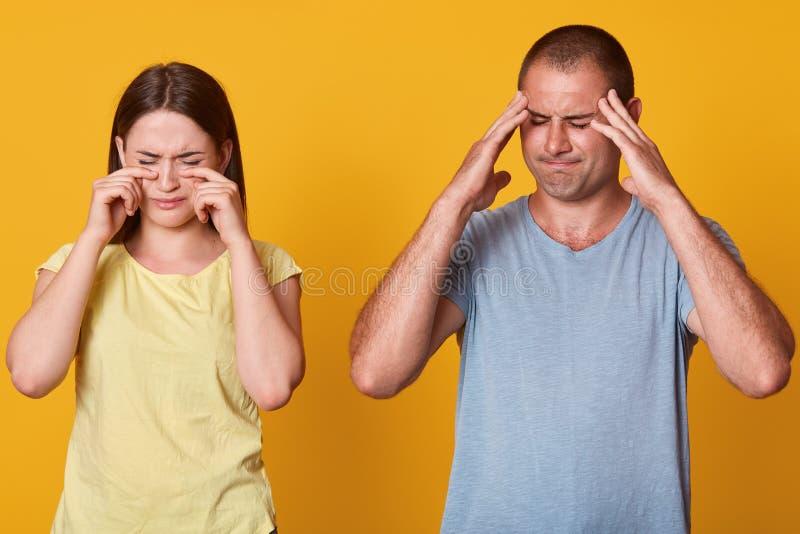 Положение 2 людей перед камерой, женщиной плача и смотря разочаровано, мужчина держит руки на висках и не любит она стоковые изображения