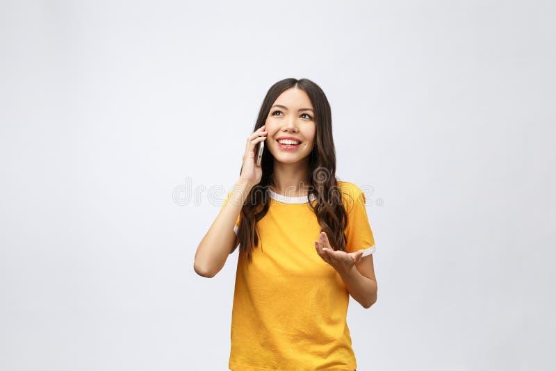 Положение мобильного телефона и улыбки красивой молодой азиатской женщины говоря на серой предпосылке, вызывать фрилансера женски стоковые фотографии rf