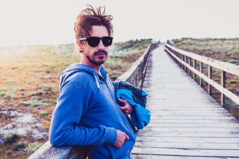 Положение молодого человека хипстера испанское выглядя на пляже песка стоковая фотография