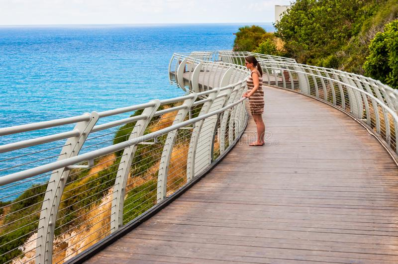Положение молодой женщины туристское на мосте скал и смотреть на северном побережье Средиземного моря от горы Rosh Hanikra внутри стоковые изображения