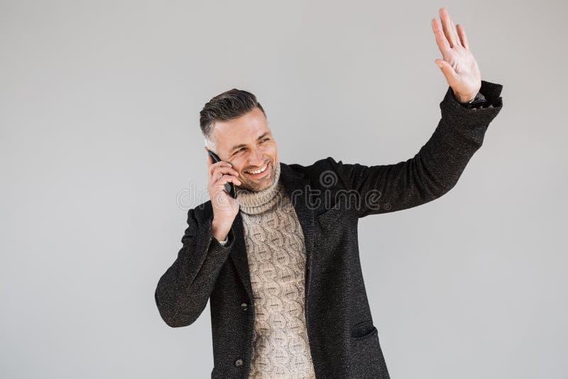 Положение пальто привлекательного человека нося стоковое изображение