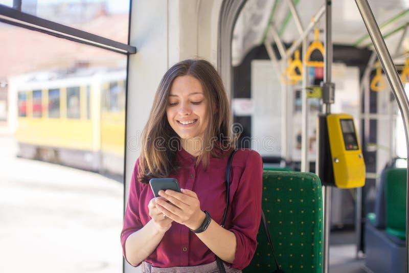 Положение пассажира молодой женщины со смартфоном пока двигающ в современный трамвай стоковые изображения