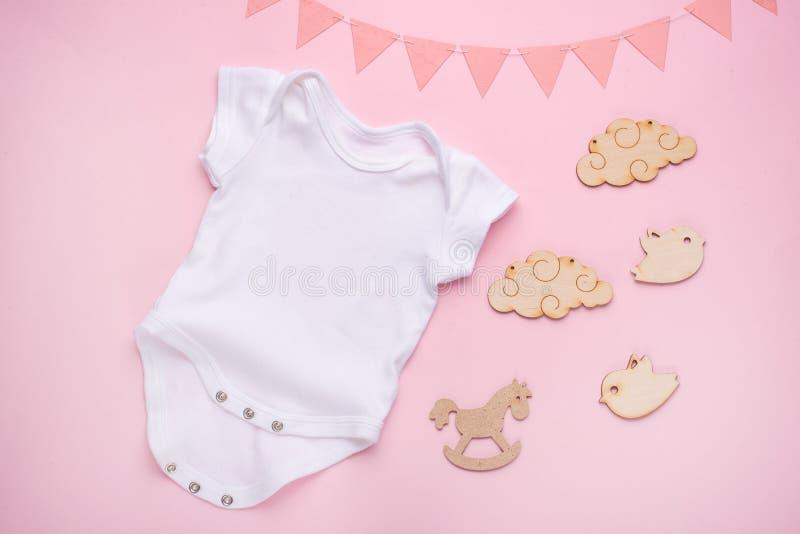 Положение плана модель-макета плоское белый bodysuit младенца на розовой предпосылке, для девушек с подарками План для размещения стоковое фото rf