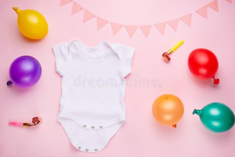 Положение плана модель-макета плоское белый bodysuit младенца на розовой предпосылке, для девушек с подарками План для размещения стоковое изображение rf