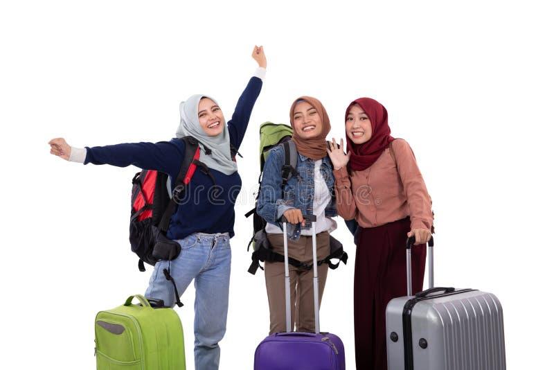 Положение промежутка времени молодой женщины hijab смеясь держа чемодан и нося сумку стоковые изображения rf