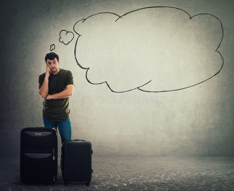 Положение путешественника молодого человека за его багажом и ожиданием стоковое изображение