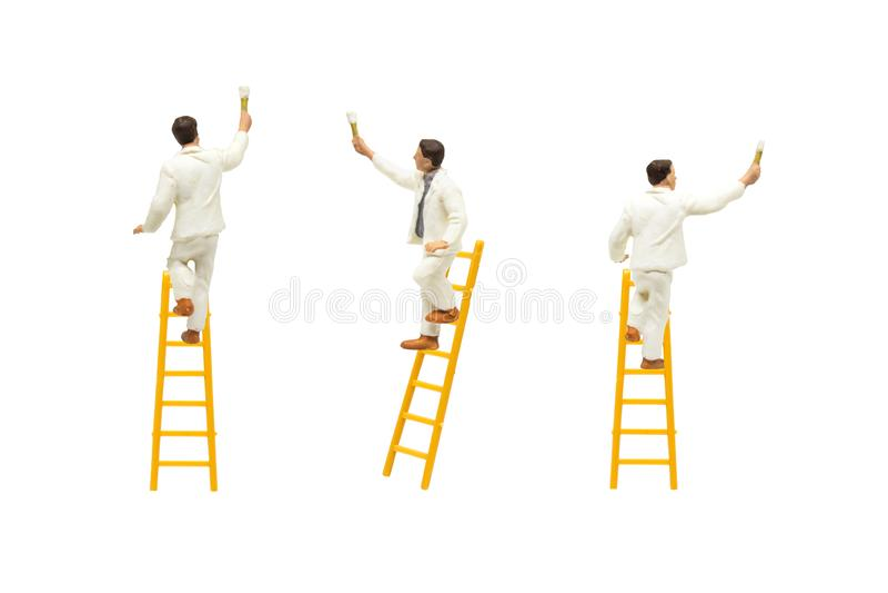 Положение художника на деревянной лестнице и крася стене с инструментами краски изолированными на белой предпосылке стоковое фото rf