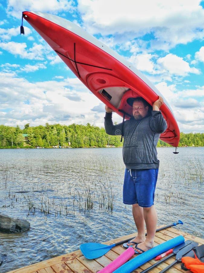 Положение человека на доке реки озера деревянном и удержание шлюпки каяка на его голове стоковое изображение rf