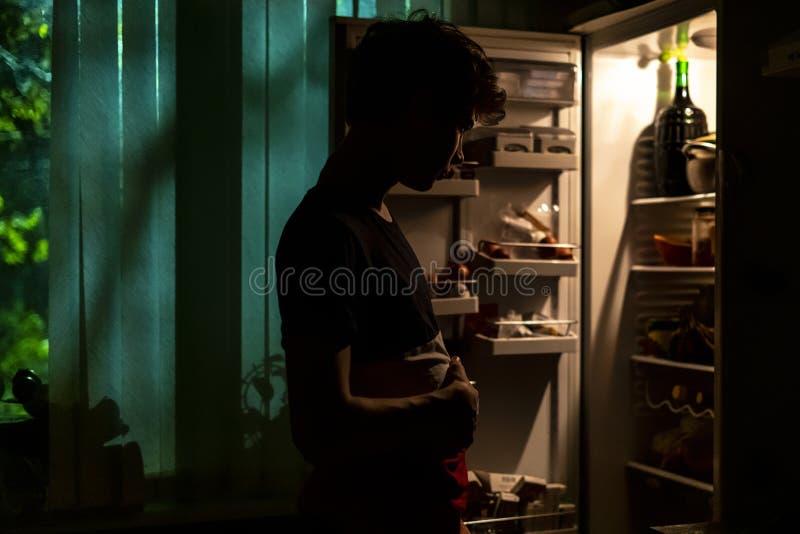 Положение человека около раскрытого холодильника для того чтобы скомплектовать некоторую еду вечером дома f стоковое изображение rf