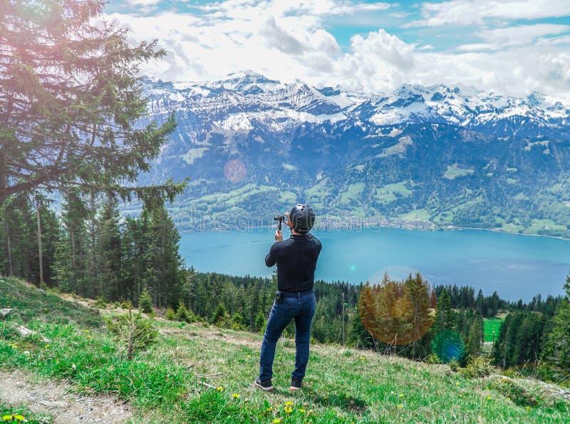 Положение человека принимает озеро и горы взгляда фото стоковое фото rf
