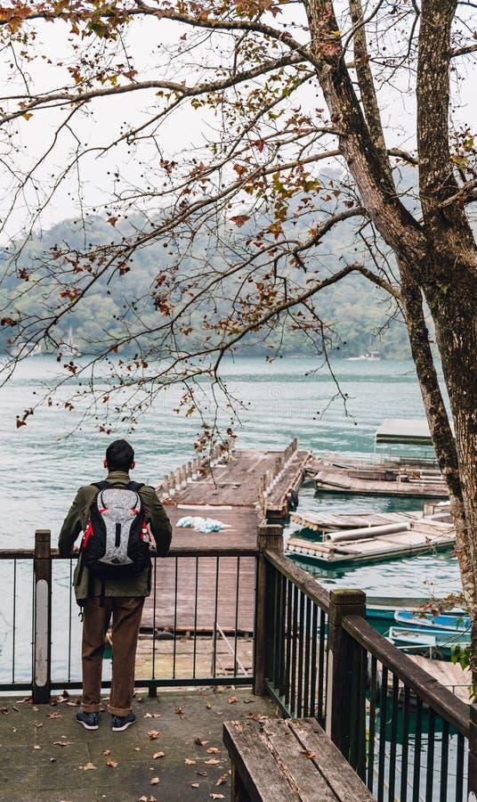 Положение человека туристское для смотреть взгляд озера лун Солнца в поселке Yuchi, Nantou County, Тайване стоковое фото