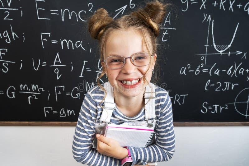 Положение школьницы девушки на классн классном и тетрадях удержания стоковые изображения