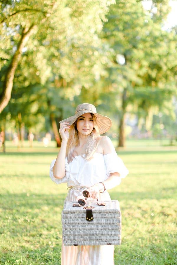 Положение шляпы молодой славной девушки нося в парке с сумкой стоковые изображения