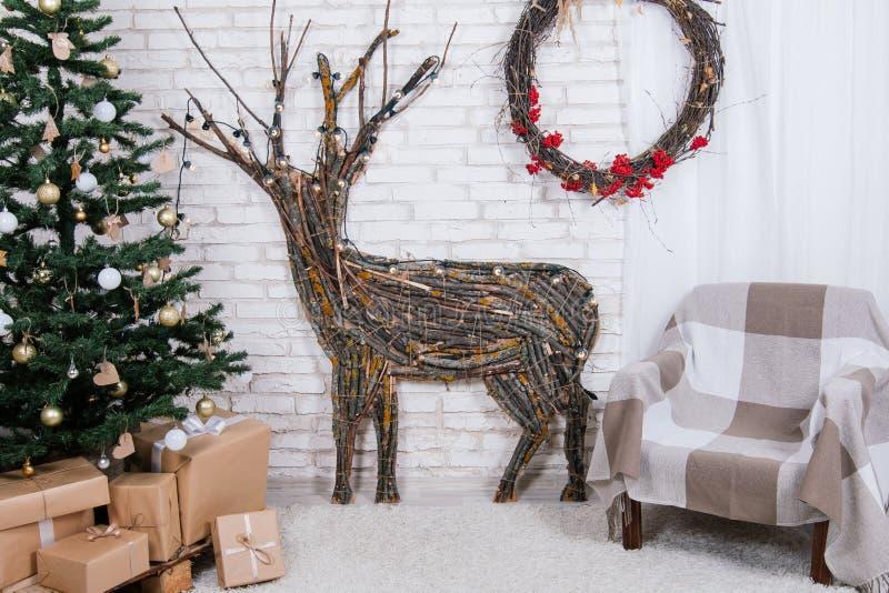Положение ` s Нового Года в студии при олень, украшенный с рождественской елкой, подарки, корзина конусов стоковое фото rf