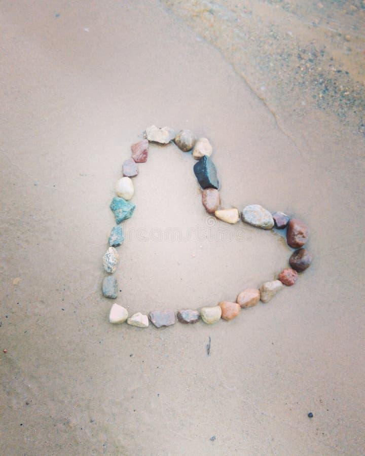 Положенное-вне сердце от камней на песке стоковое фото rf