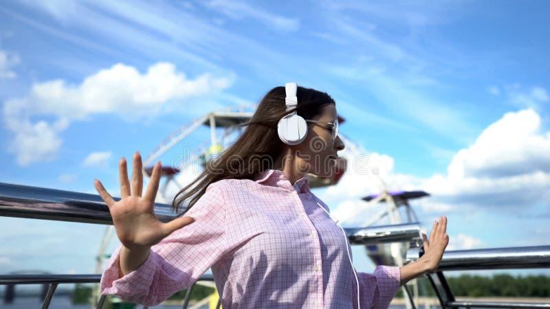 Положительная женщина брюнета в наушниках танцуя на пристани, имеющ потеху на каникулах стоковые изображения
