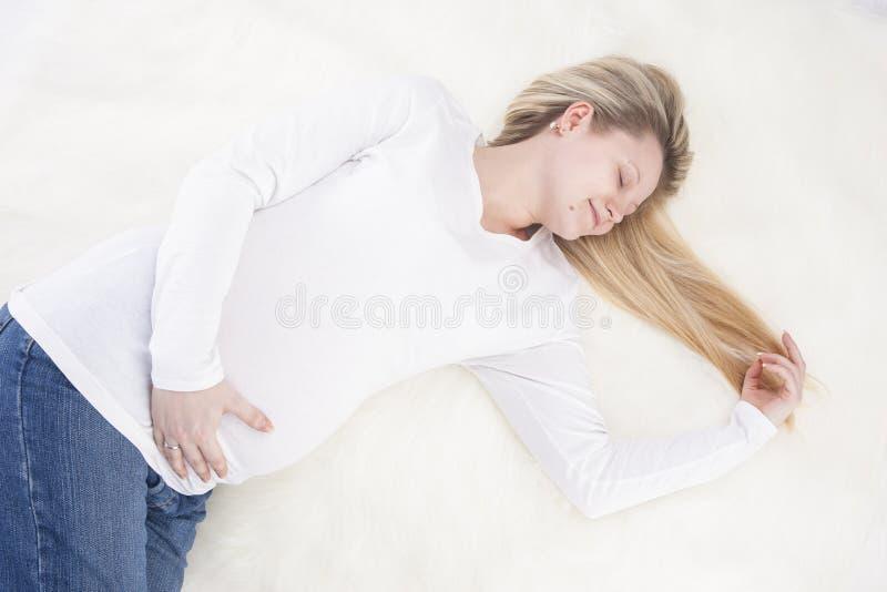 Положительная и спокойная расслабляющая беременная женщина кладя на ковер меха стоковая фотография