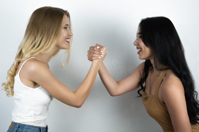 Положительная конфронтация между блондинкой и предпосылкой брюнета белой стоковое фото