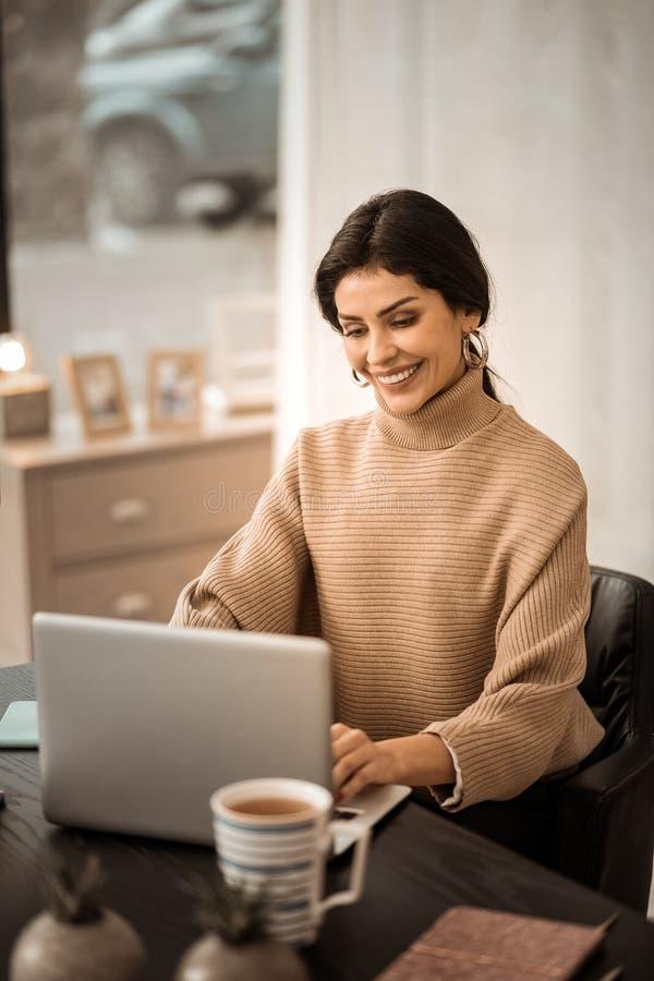 Положительная красивая дама в бежевом свитере сидя на столе с чашкой чаю стоковые фотографии rf
