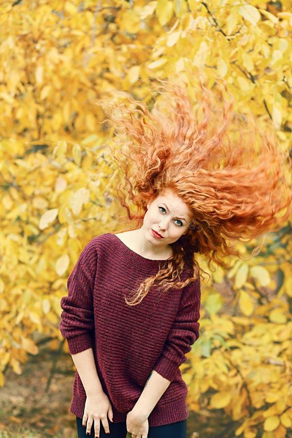 Положительная красивая молодая женщина с красными длинными волосами на предпосылке леса осени, волосах в различных направлениях стоковые фото
