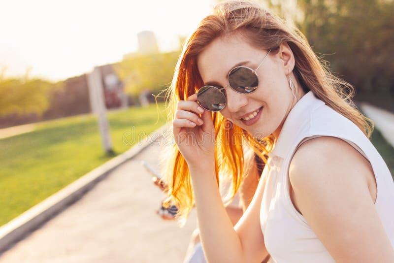 Положительная красивая счастливая красная с волосами девушка в солнечных очках зеркала с друзьями на предпосылке улицы города, вр стоковая фотография rf