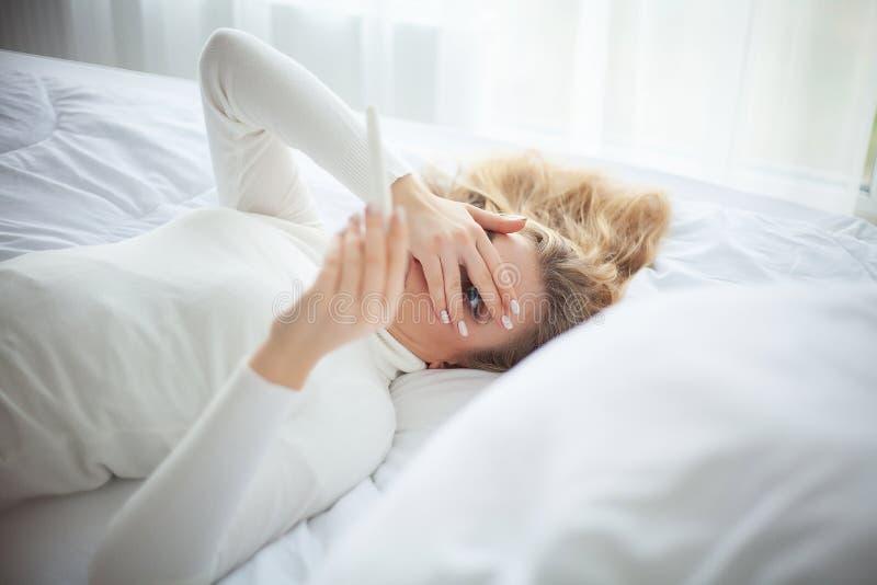 Положительная молодая женщина теста на беременность чувствуя подавленный и грустный после смотреть результат теста на беременност стоковое фото