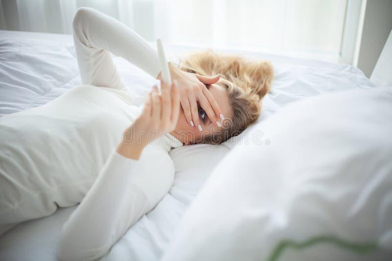 Положительная молодая женщина теста на беременность чувствуя подавленный и грустный после смотреть результат теста на беременност стоковое изображение rf