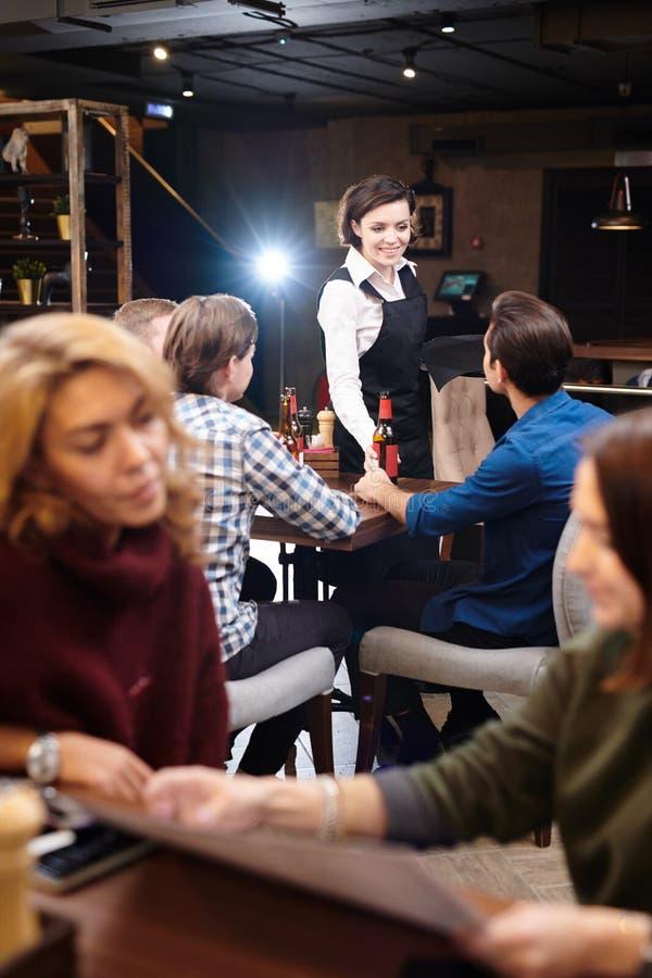Положительная официантка давая пиво бутылки людям стоковые изображения