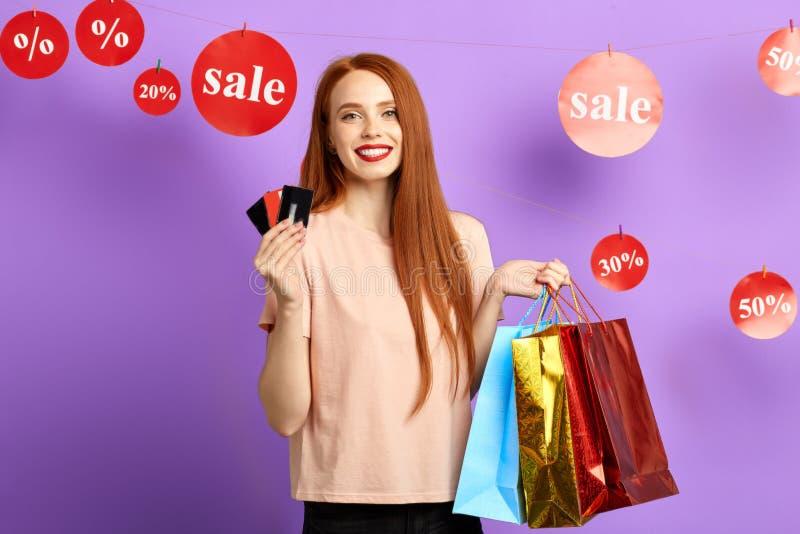 Положительная очаровательная девушка с хозяйственными сумками держа кредитные карточки стоковые фотографии rf