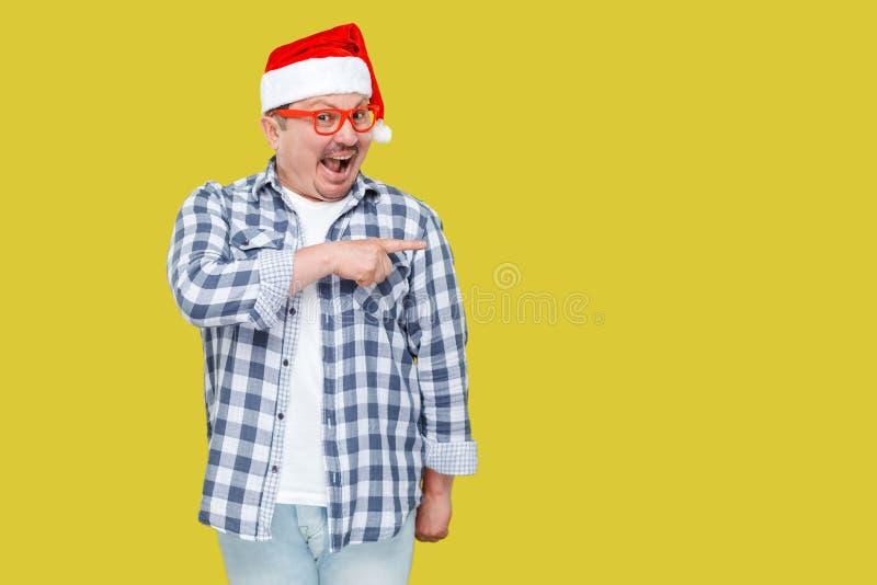 Положительная середина постарела человек в красной крышке santa Нового Года и вскользь st стоковые фотографии rf