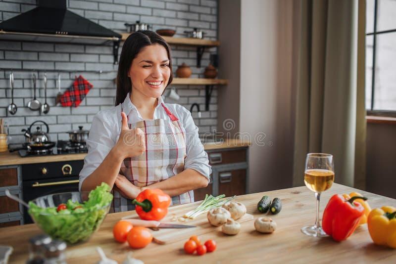 Положительная счастливая женщина сидит на таблице в кухне Она смотрит на камере и большом пальце руки шоу большом вверх Женщина з стоковые фото