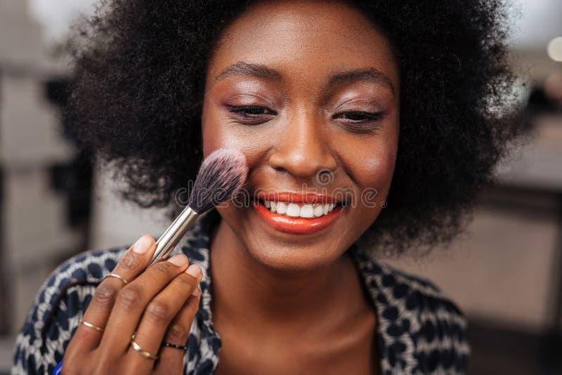 Положительная темнокожая женщина с вьющиеся волосы делая краснеет на ее стороне стоковое фото