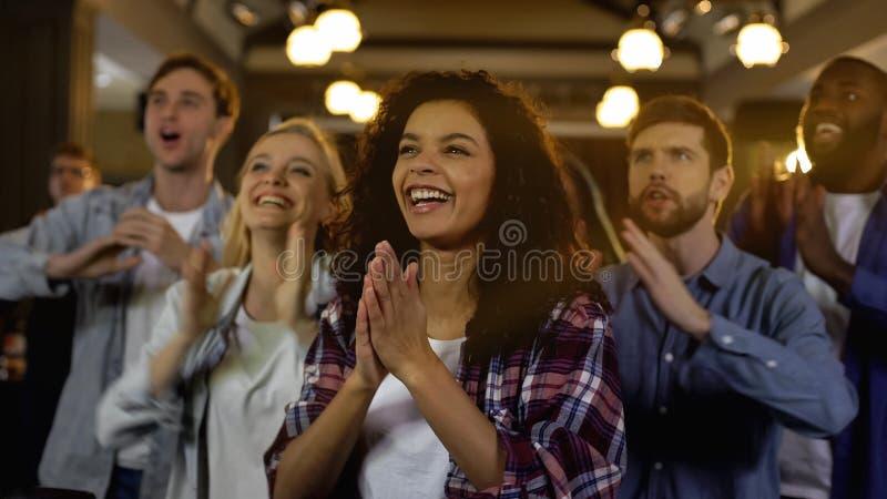 Положительные болельщики веселя, хлопающ в ладоши совместно и крича возгласы стоковое изображение
