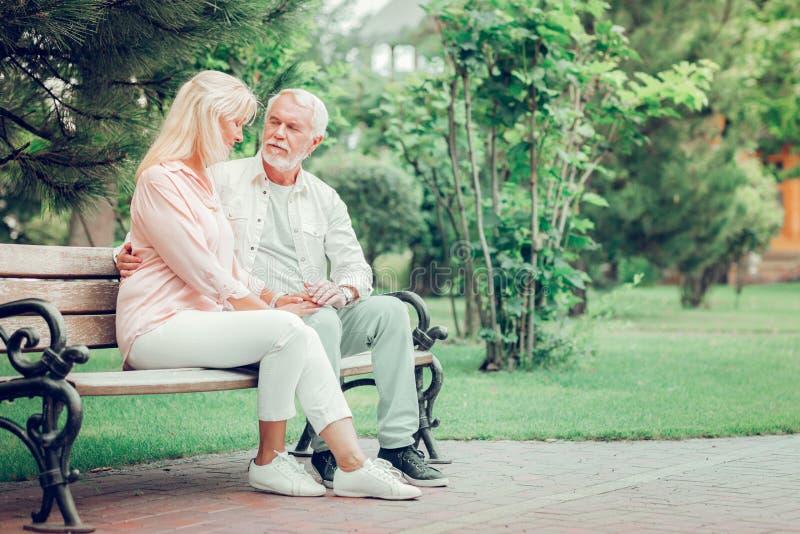 Положительные достигшие возраста пары отдыхая на стенде стоковые фотографии rf