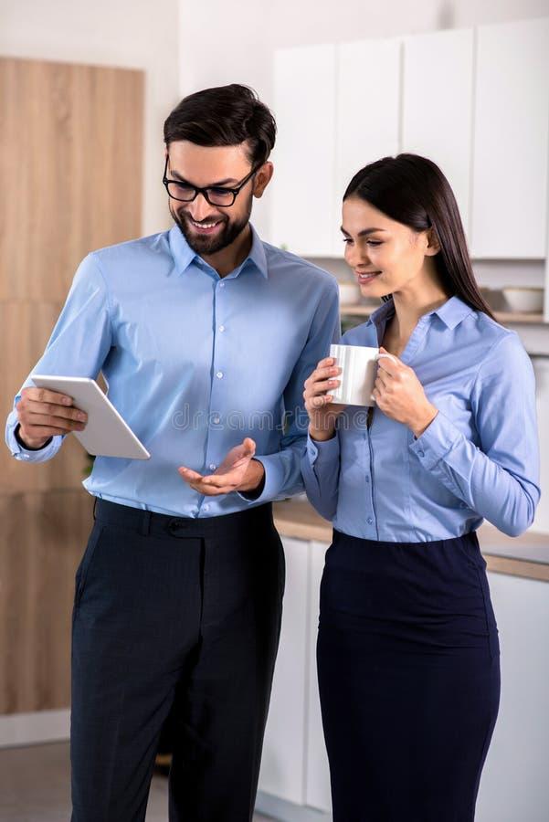 Положительные коллеги дела используя таблетку в кухне стоковые фото