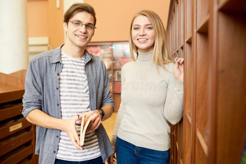 Положительные пары студентов выбирая книги в библиотеке стоковая фотография rf