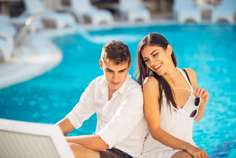 Положительные счастливые пары ослабляя бассейном в роскошном курорте летних каникулов Наслаждающся временем совместно в центре зд стоковые изображения