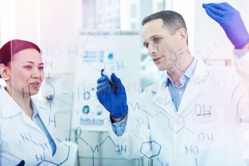 Положительные умные химики обсуждая химическую формулу стоковые изображения rf