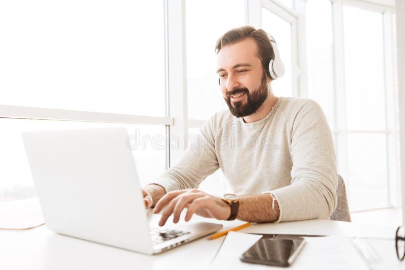 Положительный европейский человек с короткие коричневые беседовать или scrollin волос стоковое фото