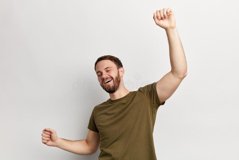 Положительный жизнерадостный человек в зеленой футболке имея потеху в студии стоковые изображения rf