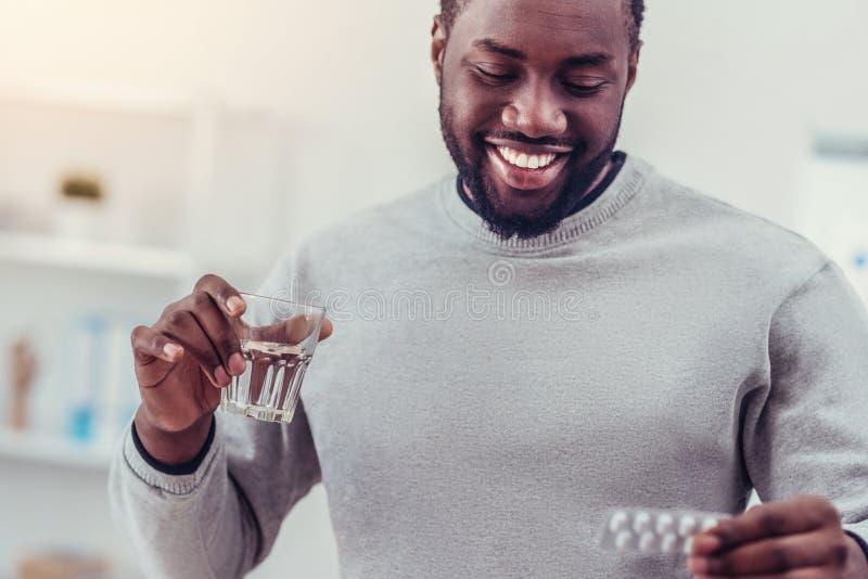 Положительный запомненный Афро-американский человек принимая лекарство стоковая фотография rf
