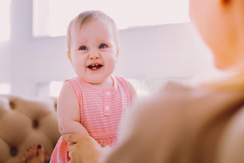 Положительный младенец усмехаясь пока сидящ на коленях матери стоковая фотография rf