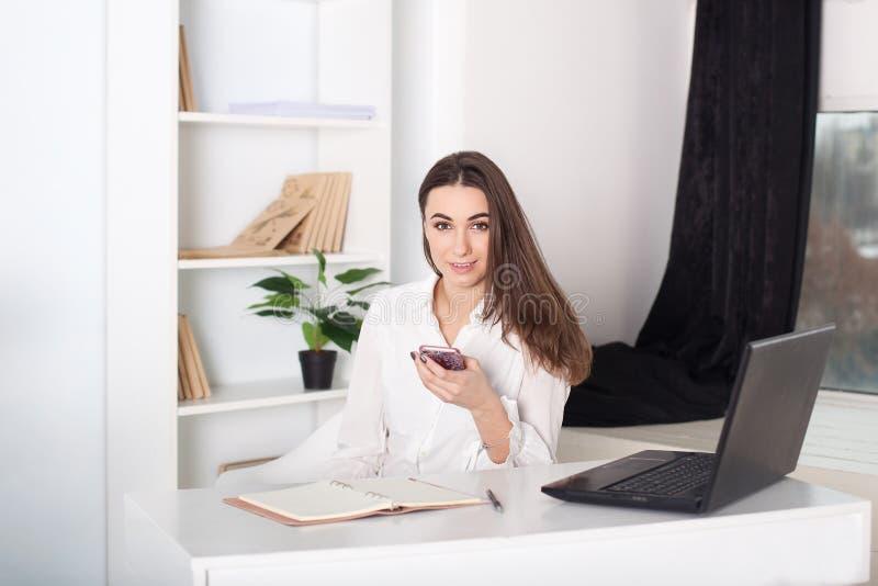 Положительный молодой менеджер работая на проекте дела в офисе Девушка вызывает по телефону Портрет конца-вверх работника офиса C стоковые изображения rf