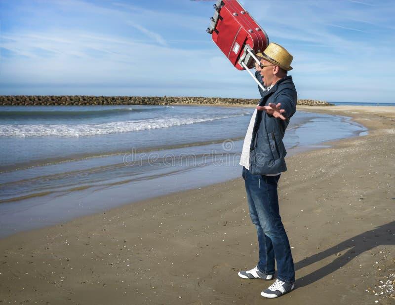 Положительный молодой человек радуется положение на seashore, поднимает красный чемодан вверх стоковое изображение