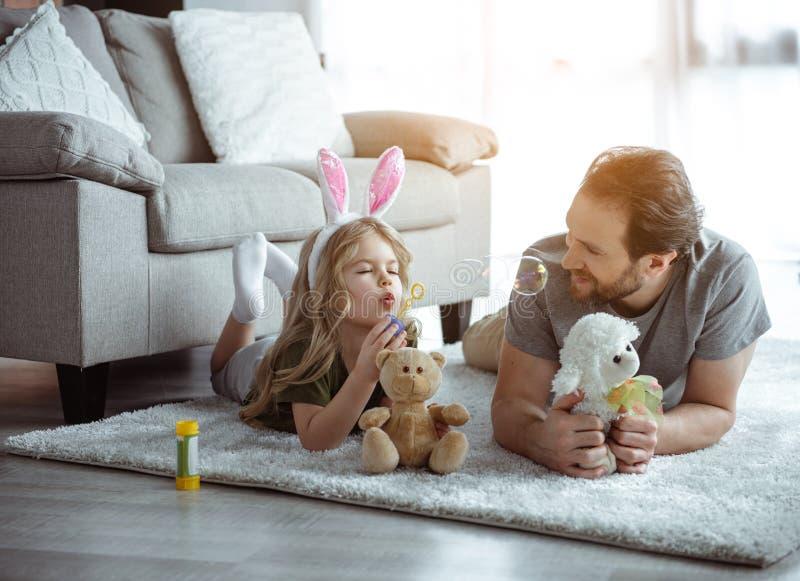 Положительный отец и дочь играя совместно дома стоковые фотографии rf