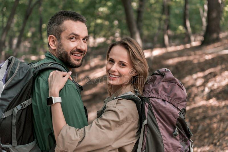 Положительный человек и женщина наслаждаясь романтичной прогулкой в лесе стоковые изображения